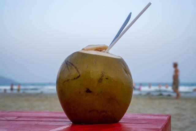 Frische geöffnete Kokosnuss mit Strohhalm und Löffel auf einem Holztisch mit Meer und Strand im Hintergrund Nahaufnahme
