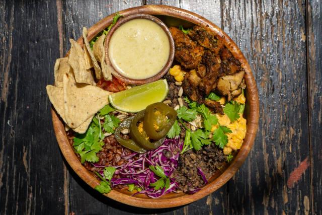 Gesunde Bowl mit Gegrilltem Hähnchen, Braunen Reis, Mais, Rotkohl, Tortilla Chips, Jalapeno Chilis, Kräutern und Soße in einer Holzschüssel von oben auf einem Holztisch fotografiert