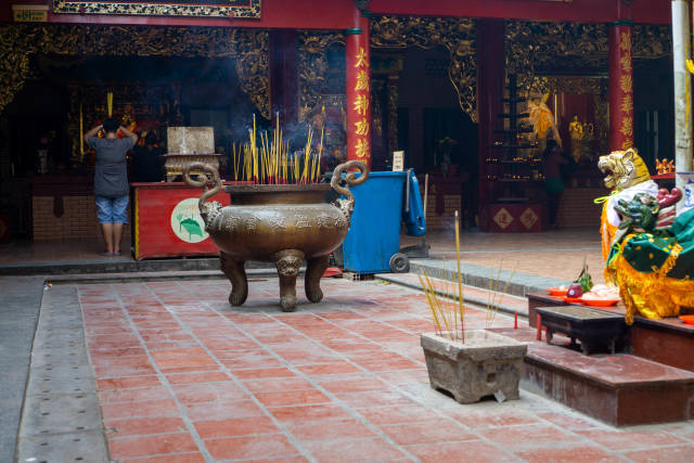 Person praying with burning Incense Sticks in front of an Altar inside Quan Am Pagoda in District 5 in Saigon, Vietnam