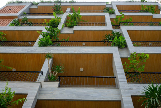 Modern Exterior of a Hotel with Wooden Elements, Balconies and Plants in Da Nang, Vietnam