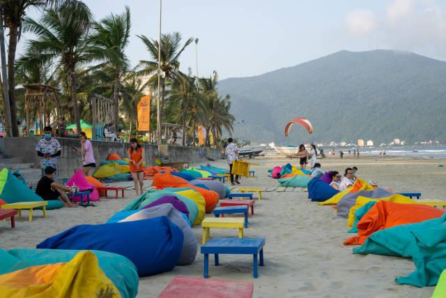 Strandbar mit Sandsäcken und Holztischen in vielen Farben mit Son Tra Halbinsel und Palmen im Hintergrund in Da Nang, Vietnam