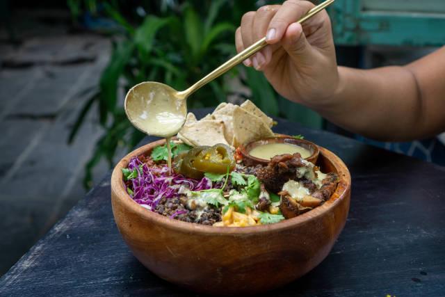 Person gibt Honig Senf Dressing auf eine gemischte Salat Bowl mit Bohnen, Jalapenos, gegrilltem Hähnchen, Mais, Tortilla Chips and Rotkohl mit einem Löffel in einem Restaurant