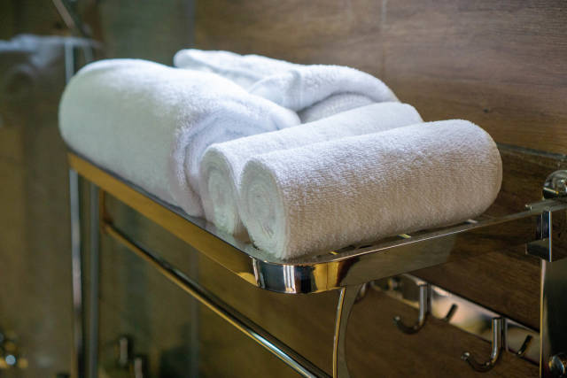 Close Up Photo of Large Bath Towels and Small Face Towels on a Towel Rack in a Hotel Bathroom with Shower in the Background