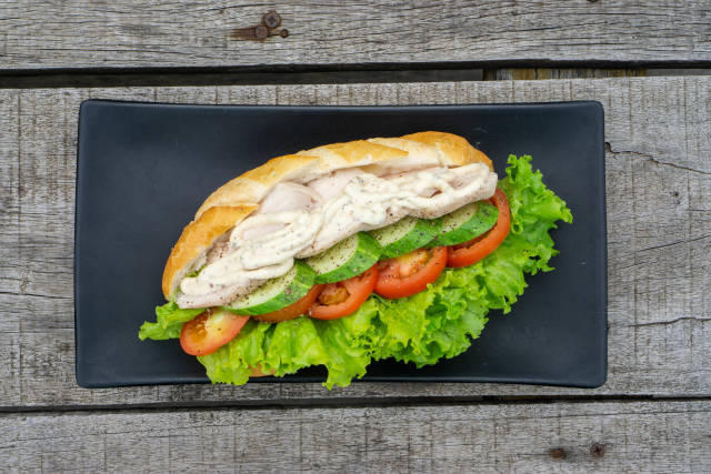 Top View Food Photo of Sandwich with Grilled Chicken Breast, Sliced Cucumber, Tomatoes, Lettuce and Mayonnaise on a Black Plate on a Wooden Table