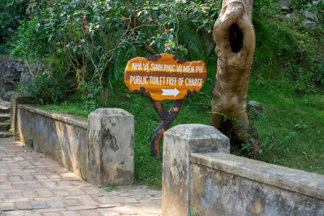 Wegbeschreibung zu einer öffentlichen Toilette auf einem Holzschild bei der Touristenattraktion Marble Mountains in Da Nang, Vietnam