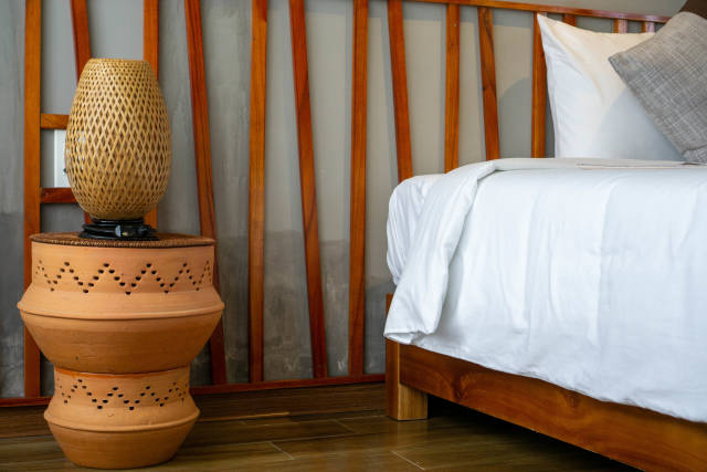 Bamboo Bed Lamp on Ceramic Bed Side Table next to a Bed with Wooden Bed Frame in a Modern Hotel Room in Hoi An, Vietnam