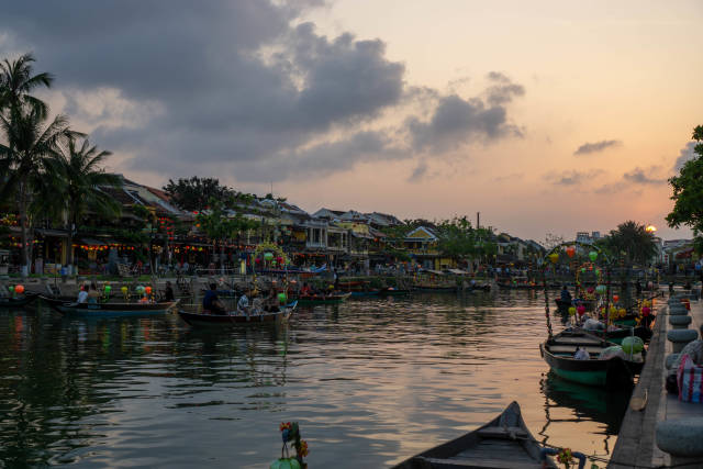 Tourist Boats with Lanterns on Thu Bon River along the many Shops and Restaurants at Sunset in the Ancient Town of Hoi An, Vietnam