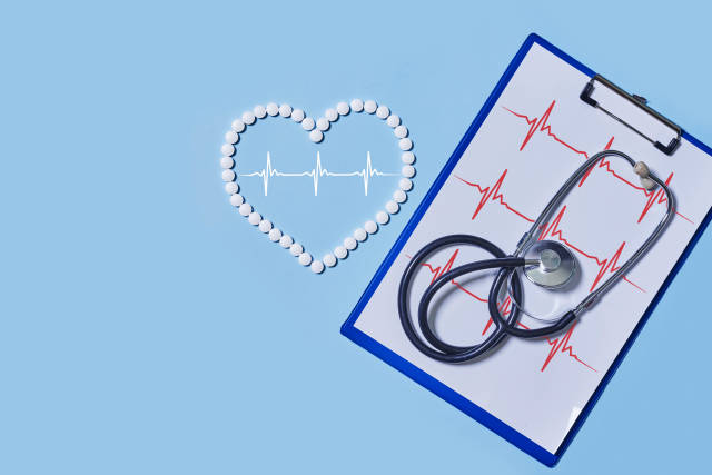 Heart ekg cardiogram, tablets and stethoscope on colored background