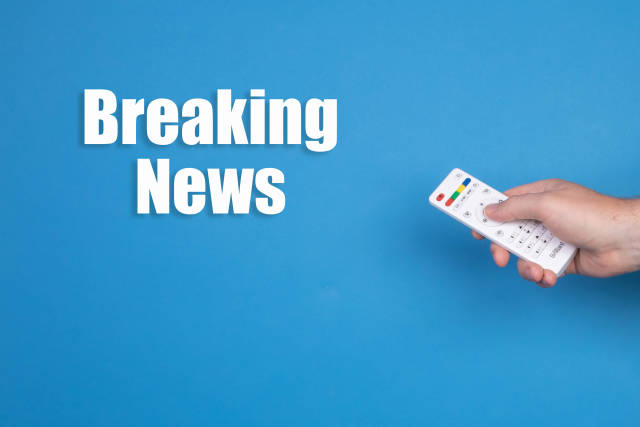 Hand holding remote control and Breaking news text on blue background