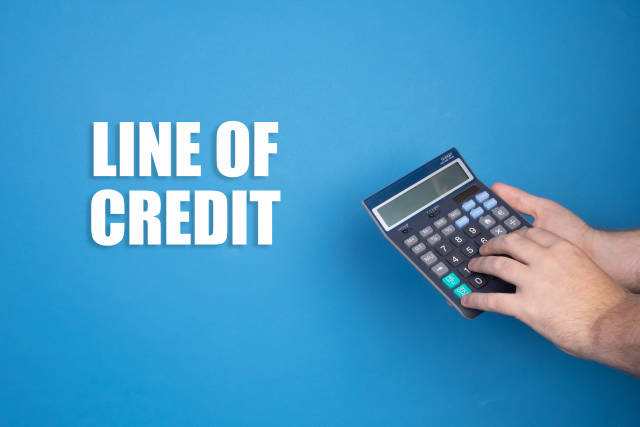 Hand holding calculator and Line of Credit text on blue background