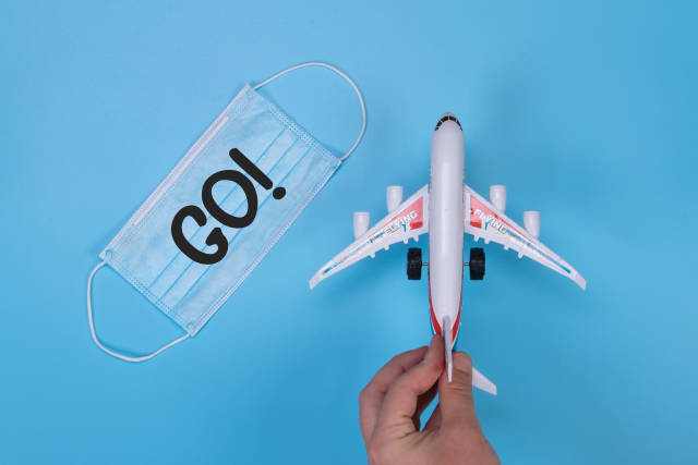 Hand holding miniature airplane and medical face mask with GO! text on blue background