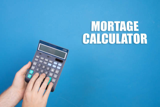 Hand holding calculator and Mortage Calculator text on blue background