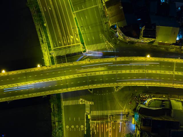 Drohnen Nachtfoto von einer Brücke in der Draufsicht mit Lichtstreifen von Fahrzeugen in Ho Chi Minh Stadt, Vietnam