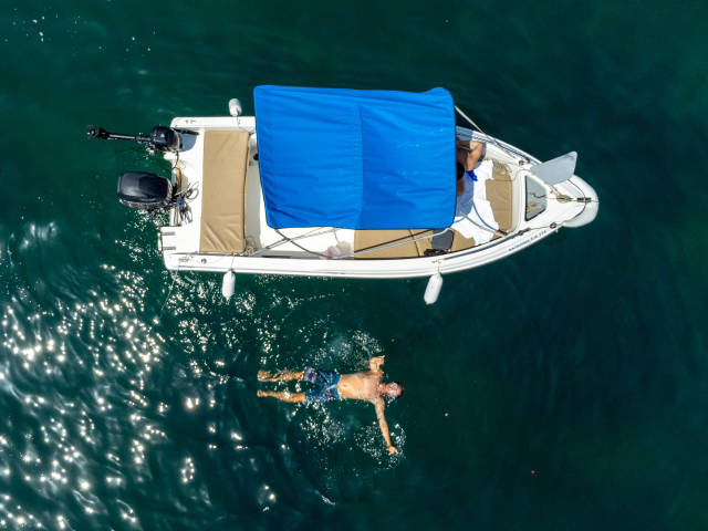 Drone photography on holiday in Greece: swimming next to the boat near Agios Dimitrios beach, Alonissos