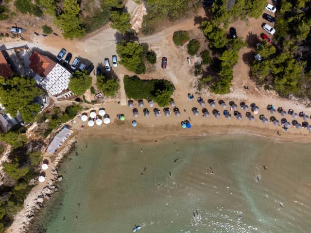 Chrisi Milia: der einzige Sandstrand auf Alonissos. Schmaler Strand mit zwei Reihen von Sonnenschirmen