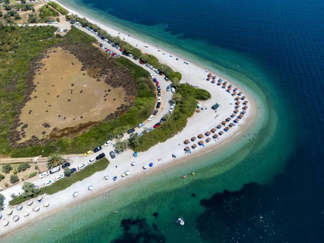 Strand in Hufeisenform in Griechenland: Draufsicht auf Agios Dimitrios (Alonissos) mit Strohsonnenschirmen