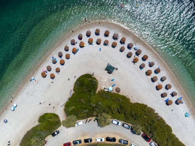 Parking spaces and straw parasols on the pebble beach of Agios Dimitrios with turquoise waters. Top view