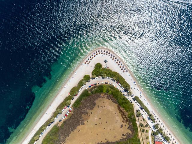 Beach with a horseshoe shape in Greece: overhead drone shot of Agios Dimitrios on Alonissos