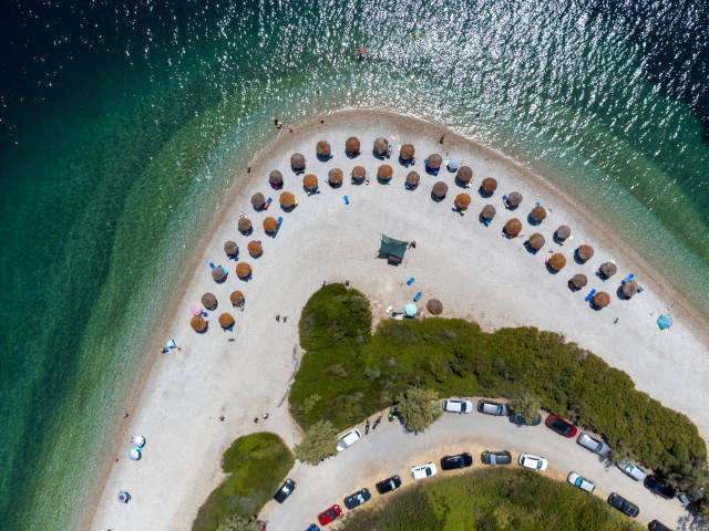 Parkplätze und Strohsonnenschirme am Kieselstrand von Agios Dimitrios (Alonnisos). Drohnenaufnahme