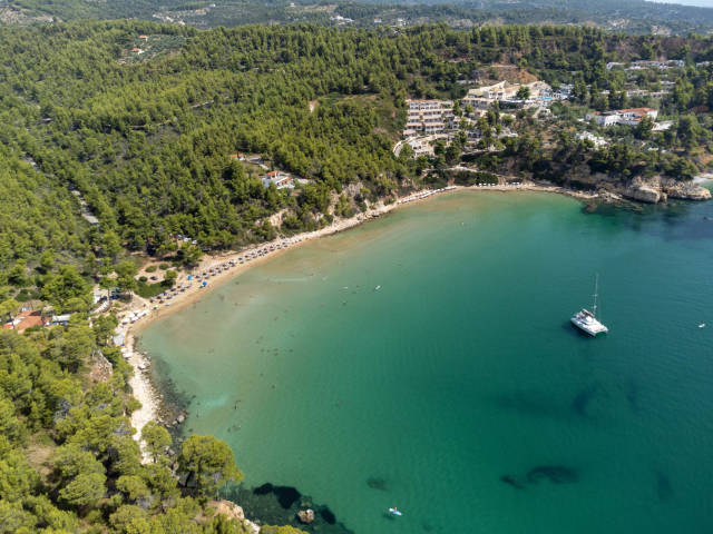 Drone photo of the breathtaking bay of Chrisi Milia surrounded by green hills with tourist accommodation