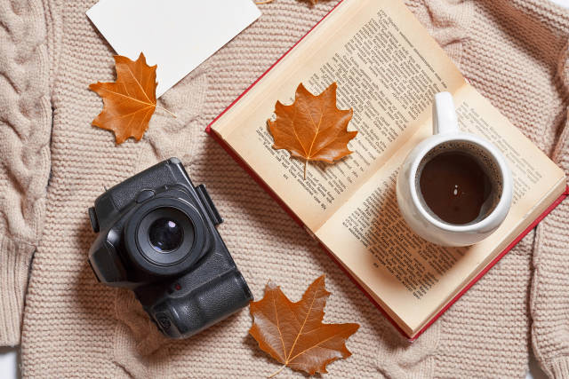 Fall leaves, warming sweater, cup of coffee, book and photo camera