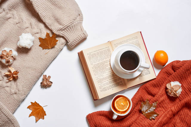 Cups of tea and coffee, cozy knitted sweaters, autumn leaves, open book on white background