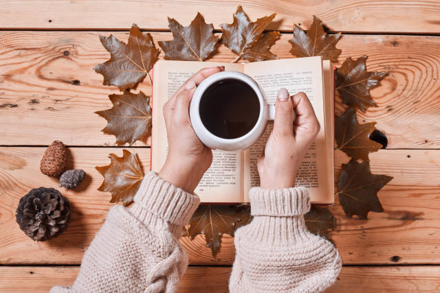 Kaffeetasse vor Buch und Blättern