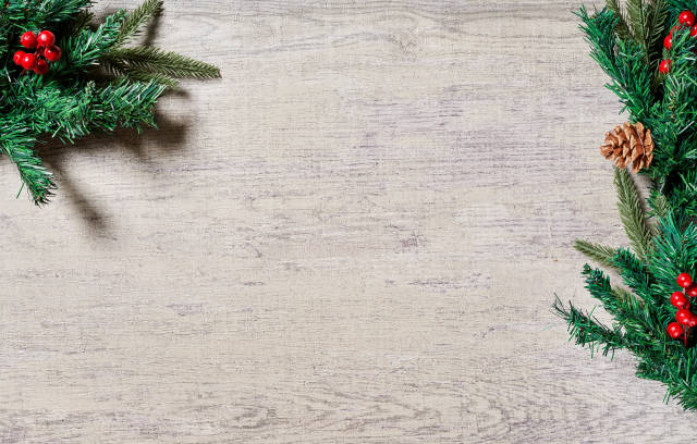 Christmas holiday background with evergreen pine branches and red berries over wood background