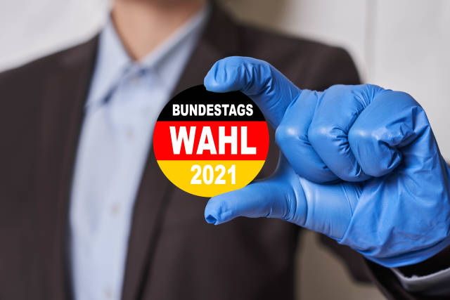 Bundestag elections badge with German flag in hands of a person in medical gloves