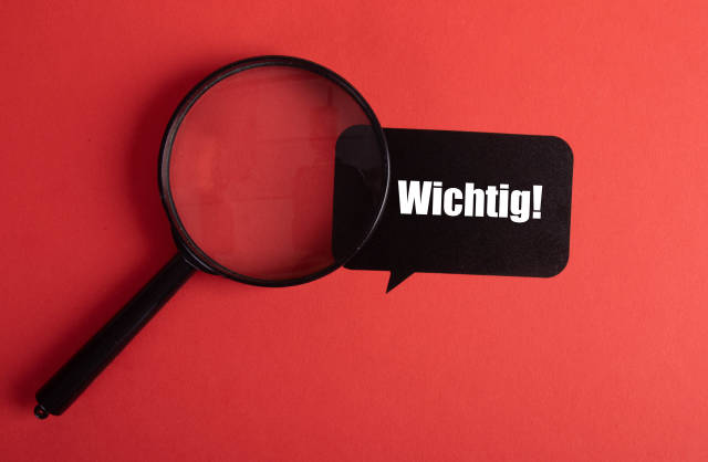 Magnifier and black sticker with Wichtig text on red background