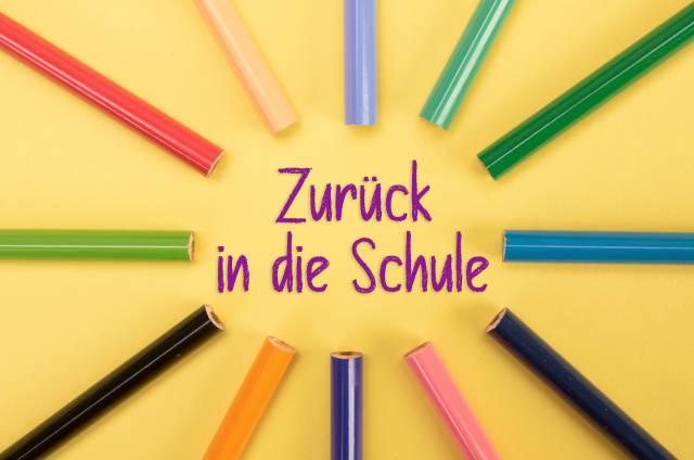 Colored pencils with Zurück in die Schule text on yellow backgorund