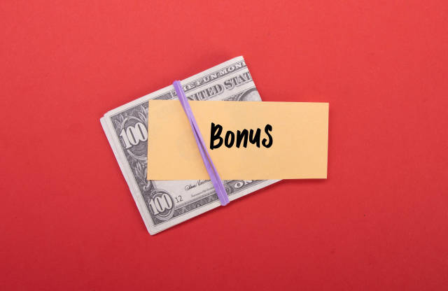 Money stack with Bonus text on red background