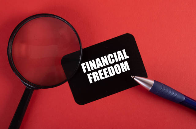 Magnifier, pen and black sticker with Financial Freedom text on red background