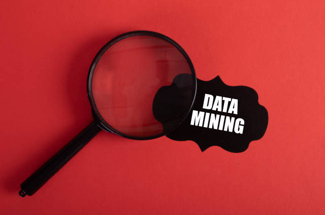 Magnifier and black sticker with Data Mining text on red background