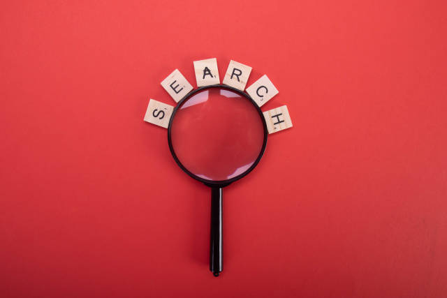 Magnifier with Search text on red background