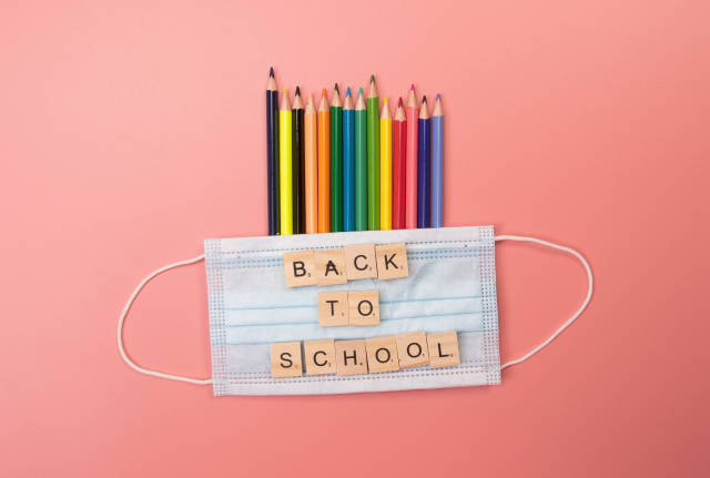 Colored pencils and medical face mask with back to School text