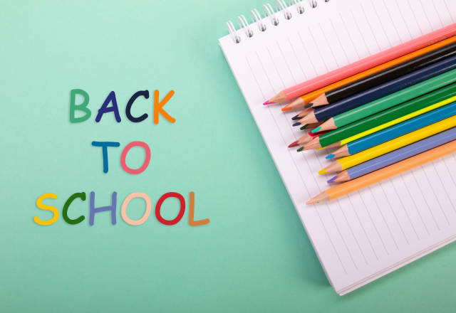 Colored pencils and notebook with Back to School text on green background