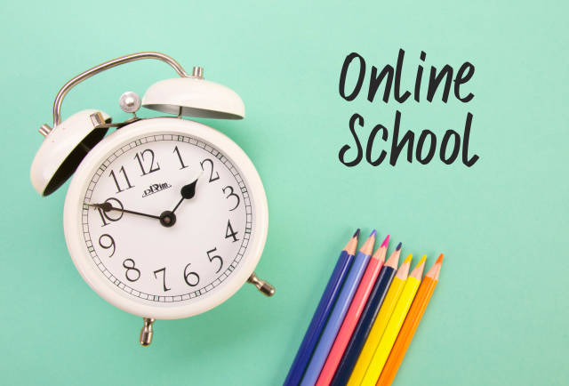 Alarm clock and colored pencils with Online School text