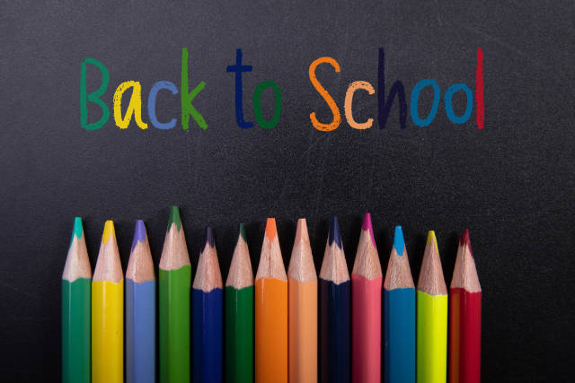 Colored pencils and Back to School text on blackboard