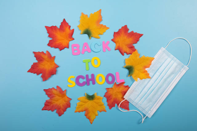 Back to School text with autumn leaves and medical face mask