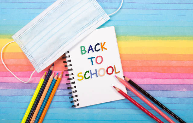 Colored pencils, medical face mask and notebook with back to School text on colorful background