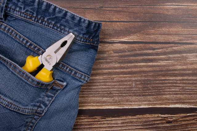 Pliers with yellow handle in a pocket of jeans