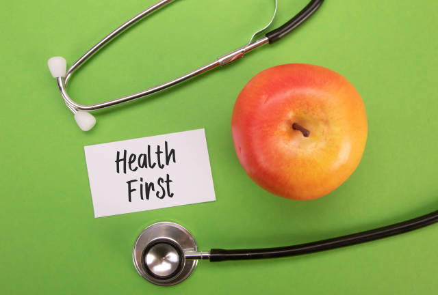 Stethoscope and red apple with Health First text