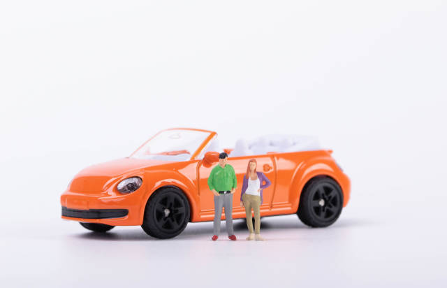 Couple standing in front of orange car