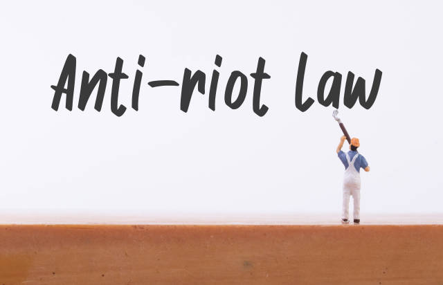 Miniature painter with Anti-riot Law text