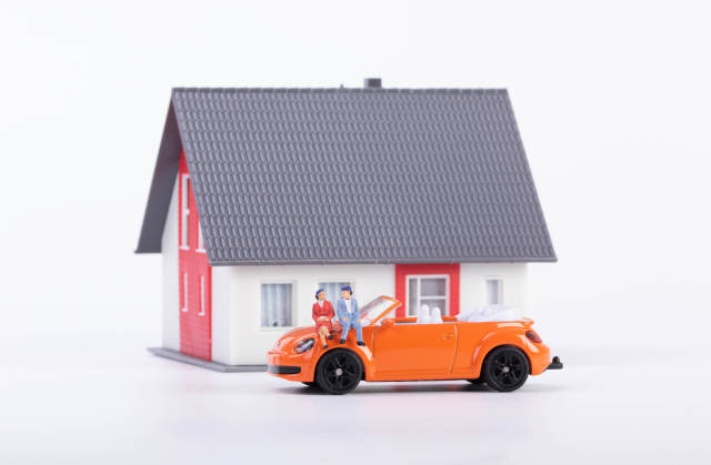 Couple sitting on a car in front of a new house