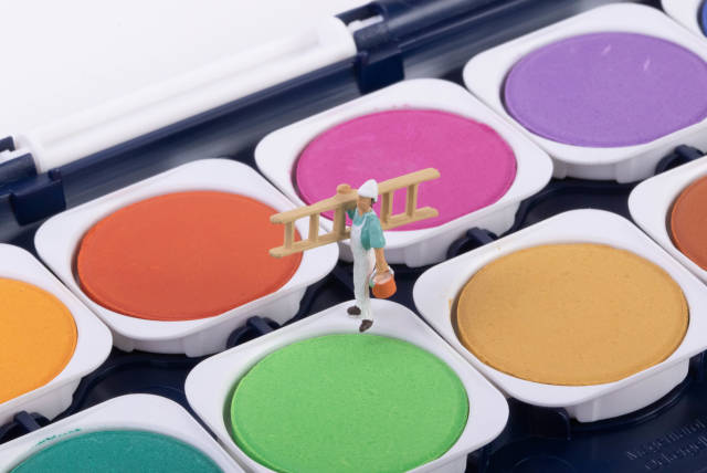 Miniature workers standing on a green paint color