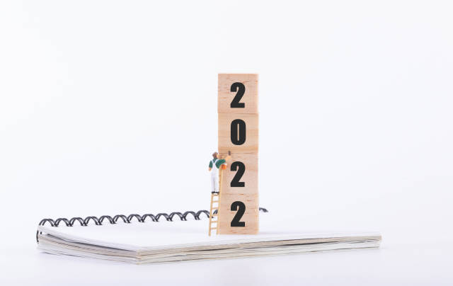 Miniature painter and wooden blocks with 2022 text on white background