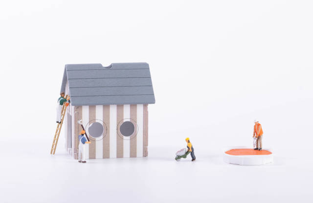 Miniature workers doing house renovation