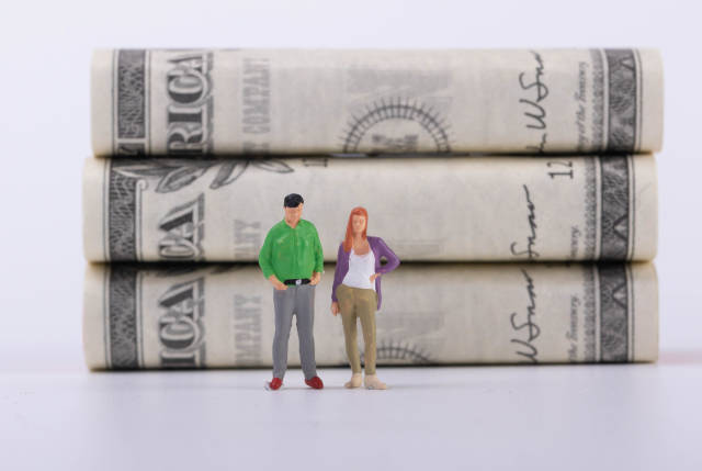 Couple standing in front of money stacks